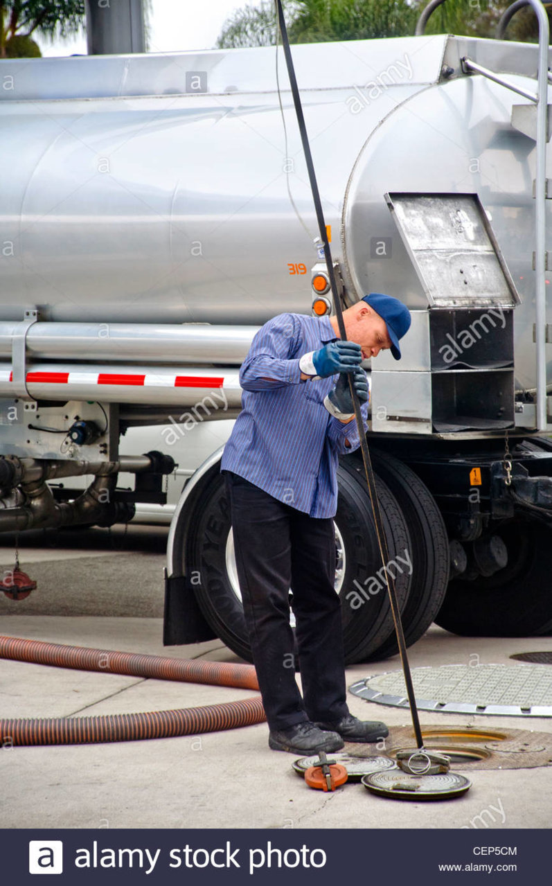 using-a-long-dip-stick-a-gasoline-delivery-man-measures-the-levels-CEP5CM.jpg